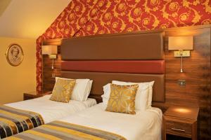 A bed or beds in a room at Rogerthorpe Manor Hotel