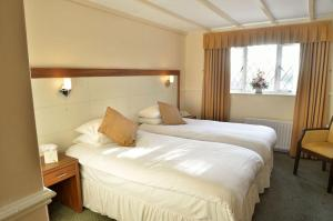 A bed or beds in a room at Damson Dene Hotel
