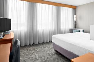A bed or beds in a room at Courtyard by Marriott Edmonton Downtown