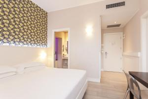 A bed or beds in a room at Hotel Villa Rosa Riviera