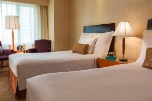 A bed or beds in a room at Renaissance Shanghai Yangtze Hotel