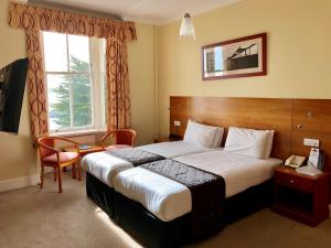 A bed or beds in a room at Marsham Court Hotel