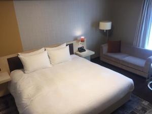 A bed or beds in a room at Richmond Hotel Narita
