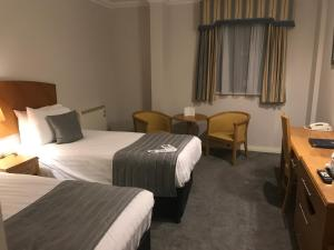 A bed or beds in a room at The Worcester Whitehouse Hotel