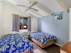 A bed or beds in a room at Bay Beach House @ Fingal Bay