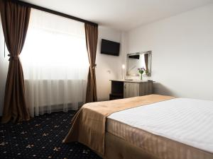 A bed or beds in a room at Pensiunea La Vie