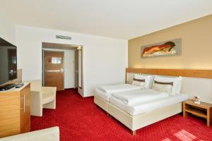 A bed or beds in a room at Austria Trend Hotel Anatol Wien