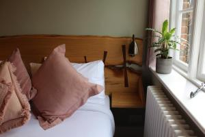 A bed or beds in a room at The Nags Head Hotel