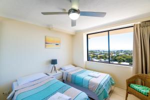 A bed or beds in a room at Burgess @ Kings Beach Apartments