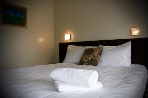 A bed or beds in a room at Birchwood Spa Motel