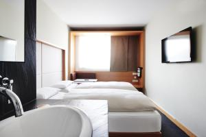 A bed or beds in a room at Hotel Daniel Graz