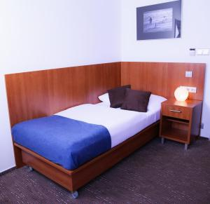 A bed or beds in a room at Academic Hotel & Congress Centre