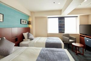 A bed or beds in a room at HOTEL MYSTAYS Yokohama