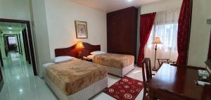 A bed or beds in a room at Ivory Hotel Apartments