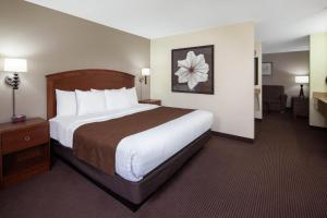 A bed or beds in a room at AmericInn by Wyndham Ironwood