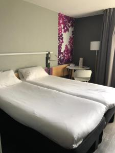 A bed or beds in a room at ibis Laon