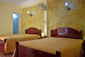 A bed or beds in a room at Hostal Dr Lara y Sra Yuda