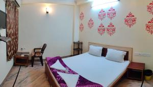 A bed or beds in a room at Madhav Guest House