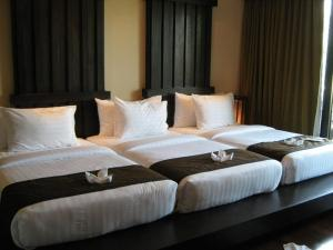 A bed or beds in a room at Yodia Heritage Hotel