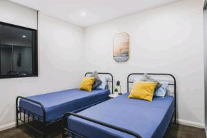 A bed or beds in a room at Sydney Olympic Park Amazing Sky View 2BR Apt
