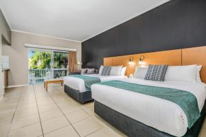 A bed or beds in a room at Hotel Grand Chancellor Palm Cove