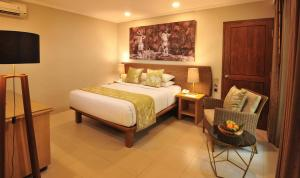 A bed or beds in a room at Puri Raja Hotel