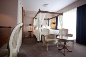 A bed or beds in a room at Hotel De Hofkamers