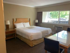 A bed or beds in a room at Okanagan Royal Park Inn by Elevate Rooms