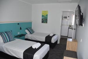 A bed or beds in a room at Ballina Homestead Motel