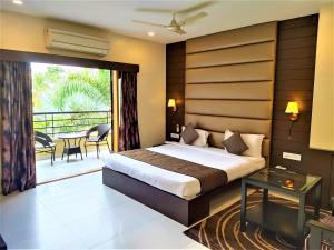 A bed or beds in a room at Carnival Resort