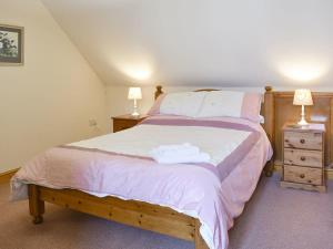 A bed or beds in a room at 2 Sawmill Cottages