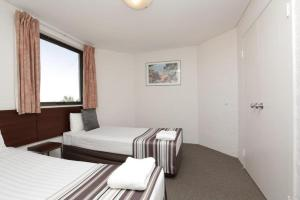 A bed or beds in a room at Atrium Hotel Mandurah