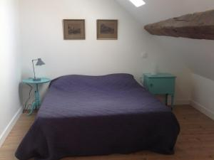A bed or beds in a room at Au Pied des Vignes