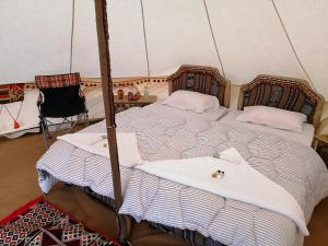 A bed or beds in a room at Al Reem Desert Camp
