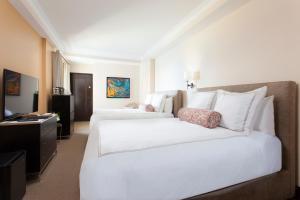 A bed or beds in a room at Condado Vanderbilt Hotel