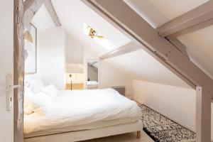 A bed or beds in a room at Le Petit Deauville
