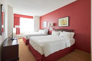 A bed or beds in a room at The Carleton Suite Hotel