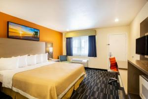 A bed or beds in a room at Days Inn by Wyndham Monterey Downtown