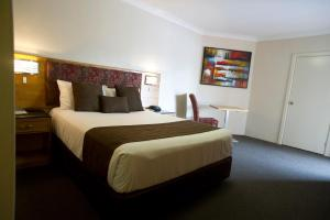 A bed or beds in a room at Noah's Mid City Motor Inn Muswellbrook