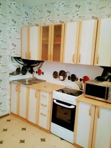 A kitchen or kitchenette at Авиаторов 40