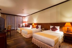 A bed or beds in a room at Angkor Paradise Hotel