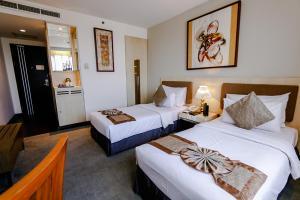 A bed or beds in a room at Grand Serela Setiabudhi Bandung