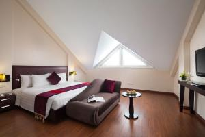 A bed or beds in a room at Hanoian Central Hotel & Spa