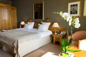 A bed or beds in a room at Le Grand Hôtel - Domaine De Divonne