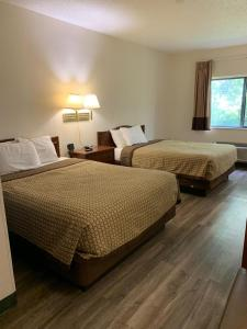A bed or beds in a room at Days Inn by Wyndham Topeka