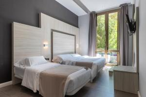 A bed or beds in a room at Plaza Goya Rooms