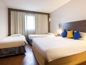 A bed or beds in a room at Novotel Manaus
