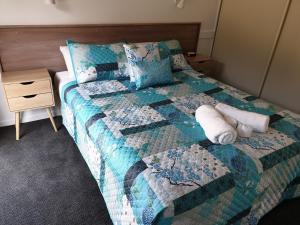 A bed or beds in a room at Tuncurry Lakes Resort