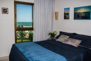 A bed or beds in a room at VG SUN Cumbuco Vista Mar