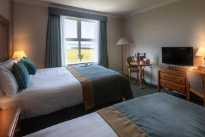 A bed or beds in a room at Inishowen Gateway Hotel